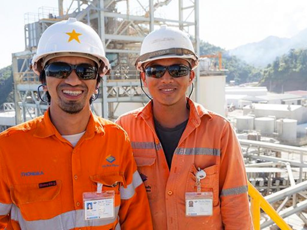 Two PanAust workers smiling at the camera