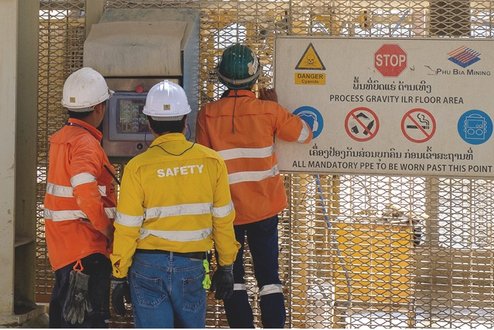 PanAust workers on site, next to a safety sign