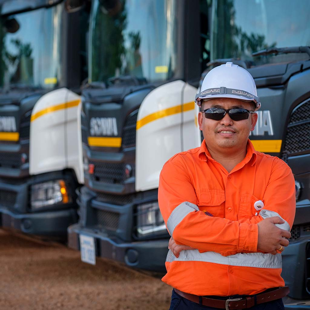 Phu Bia Mining driver in front of a fleet of Scania trucks